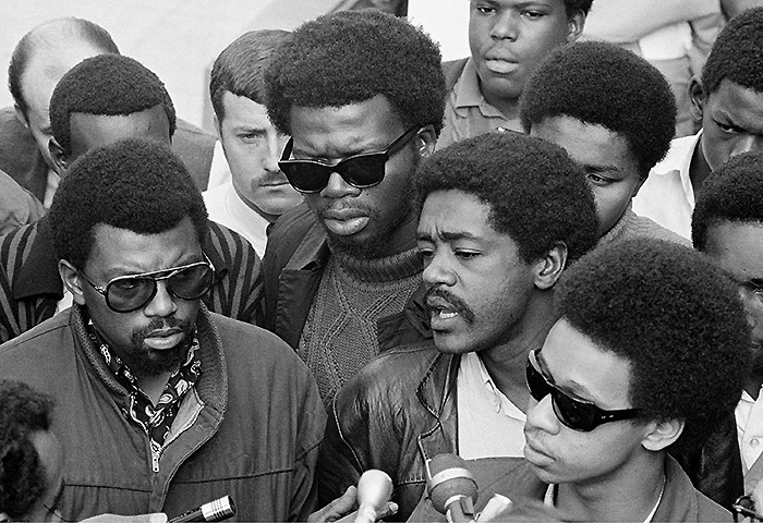 Bobby Seale, right, chairman of the Black Panther Party, is one of three speakers at a sidewalk news conference in Oakland, Ca., Nov. 21, 1968. The other speakers are Ben Stewart, left, head of the Black Students organization at San Francisco State, and George Murray, center dark glasses, suspended teacher at State. (AP Photo/Ernest K. Bennett)